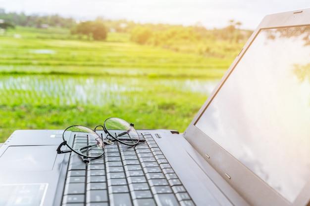 Компьютер ноутбук в очках с сельской рисовой поля сцены