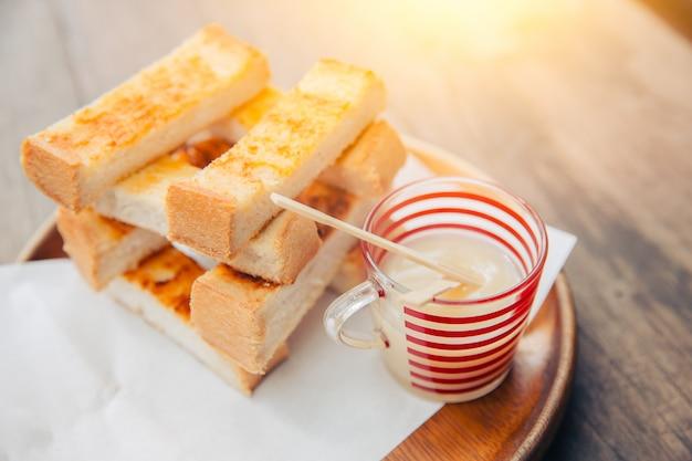 甘いコンデンスミルクでスライスしたトースト白パンは、木製のテーブルに浸しておいしいと脂肪を味わいます