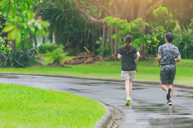 健康的な概念のために毎日ジョギング公園で走っているアジア人。