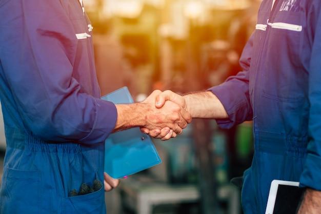労働者チームが手を振って工場のエンジニアの仕事や取引の仕事に協力しました。