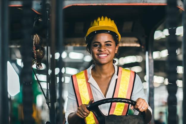 Трудовой рабочий женщин в положении водителя грузоподъемника с защитным костюмом и шлемом