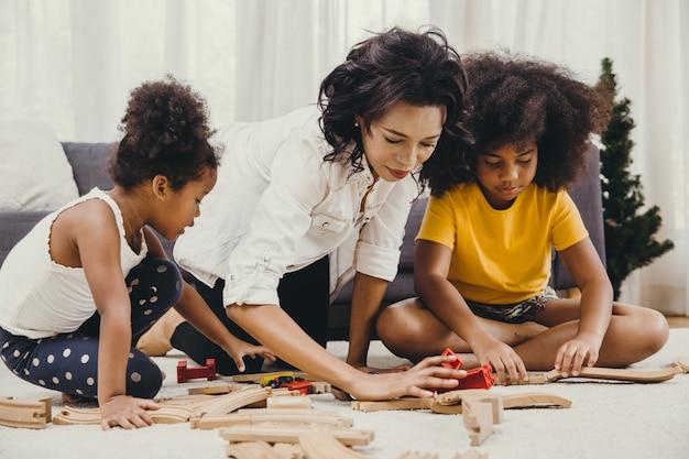 Мать родитель, играя с детьми, учиться решать головоломки игрушки на дому квартиры. няня ищет или присматривает за детьми в гостиной чернокожих.
