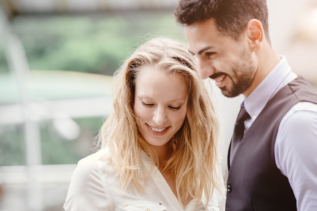 ビジネスの人々大人は混合の恋人のカップルや友人の幸せな笑顔を屋外で一緒に恥ずかしがり屋を混ぜます。