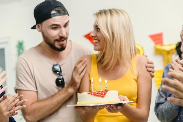友達の誕生日ケーキと美しい女性へのパーティーで女性を驚かせ、彼女はとても幸せで笑顔です。