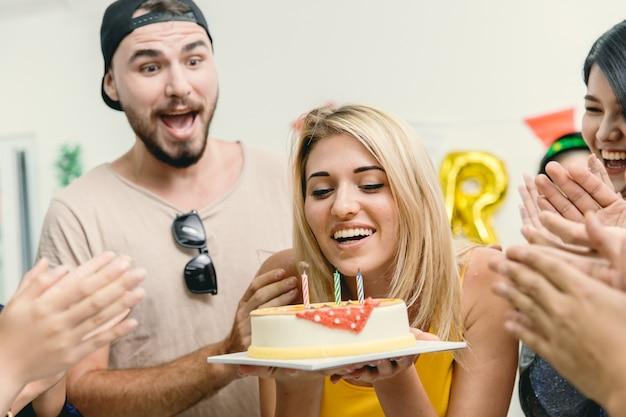 友達とのパーティーで誕生日ケーキを吹くアメリカのブロンドの美しい女の子は、彼女の誕生日のお祝いの歌をたたきます。
