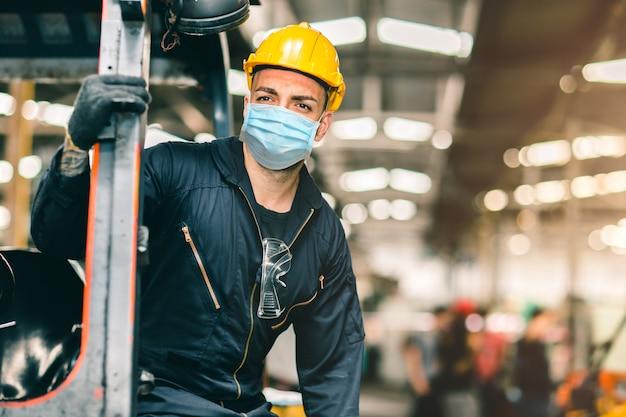 労働者は、健康な労働ケアのための工場で、コロナウイルスの拡散と煙塵の空気汚染フィルターを保護するための使い捨てフェイスマスクを着用します。