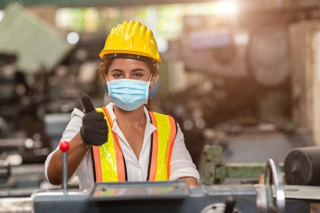 女性労働者は、健康な労働介護のために、工場でコロナウイルスの拡散と煙塵の空気汚染フィルターを保護するために使い捨てのフェイスマスクを着用します。