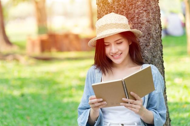 Красивая женщина азии чтение книги в парке на праздник самообучения