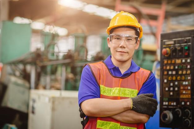 Портрет модели умного инженера азиатского китайского счастливого трудового красивого в предпосылке тяжелой индустрии. сложенные крестом и усмехаться.