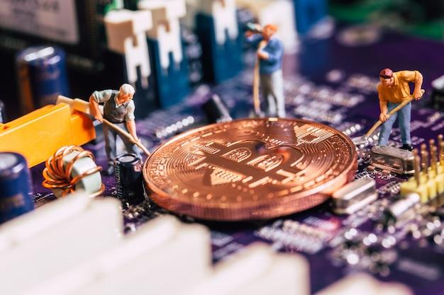 Миниатюрный работник выкапывает золото-биткойн-шахтер на электронной плате