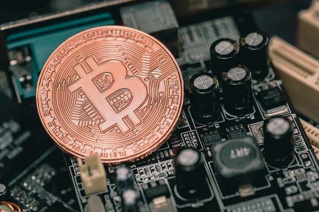 Золотой биткойн с компьютерной шахтерской электронной печатной платы.