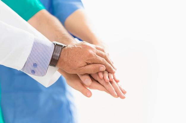 医者と医者の手は人々のコンセプトを助けるために一緒にチームワークに参加してください。