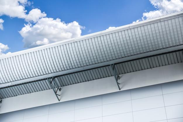 青い雲の空に対して金属板工場または倉庫高屋根工業デザイン建築