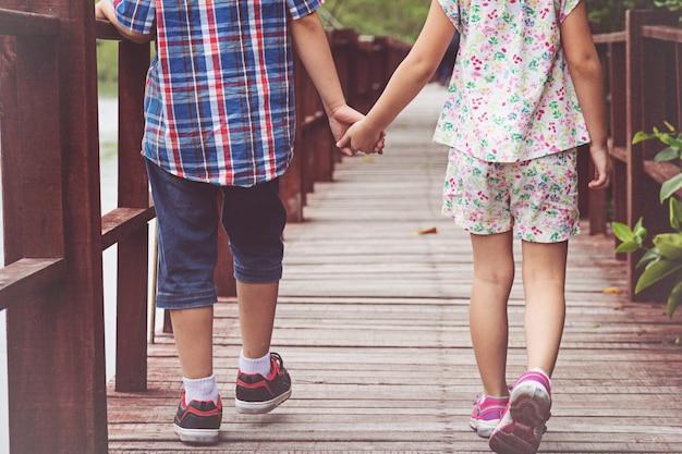 木の橋で一緒に歩いている姉妹と兄弟の手