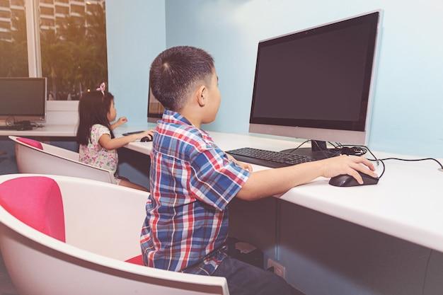 コンピュータで遊んでいる少年と少女