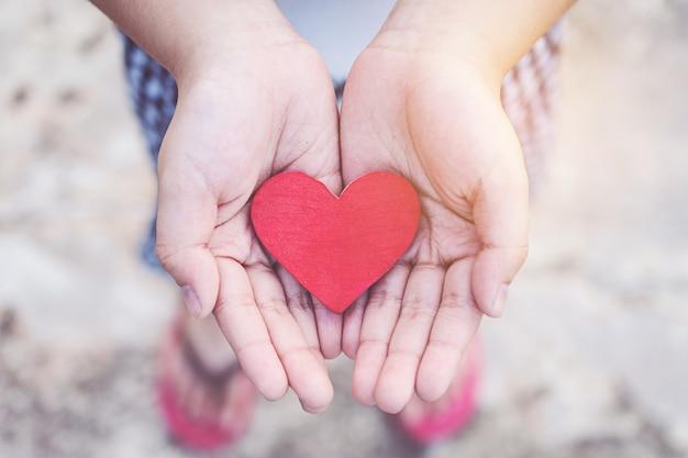 小さい子供の手は心を保持する