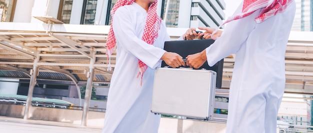 アラブビジネスマンの人々がバッグを交換しています。