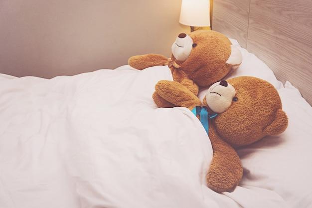 テディベアはベッドで横になっています。