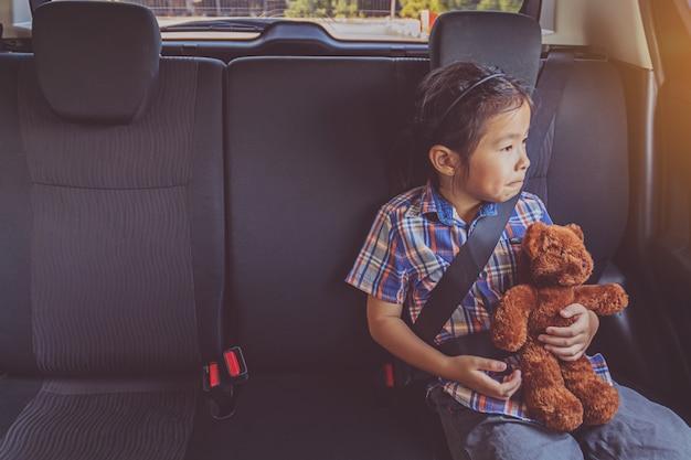 車でシートベルトを着ての幸せな女の子
