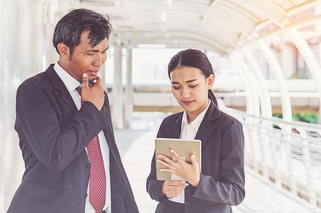 タブレットを探している都市で働くビジネスチーム