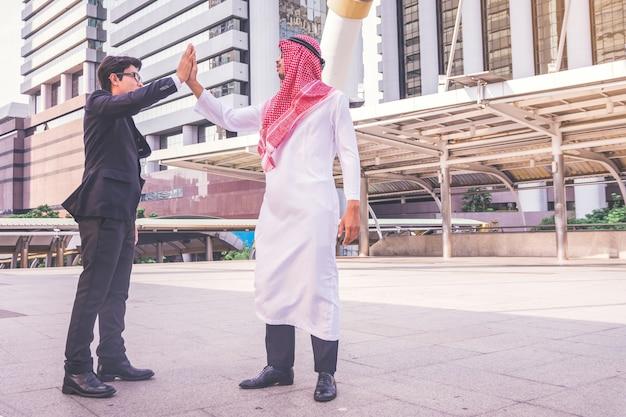 建設現場で、彼のビジネスパートナーにハイタッチを与えるアラビア語の実業家