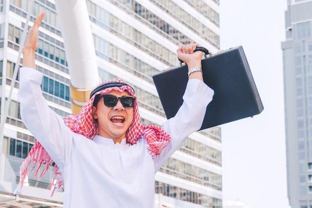 街で両手を上げることによって立っているアラブのビジネスマン