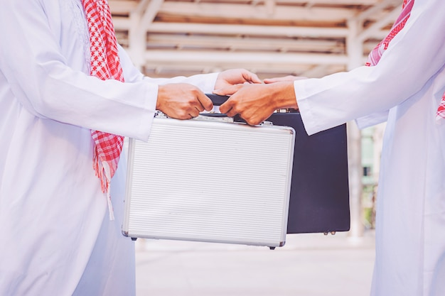 アラブのビジネスマンの人々はバッグを変えています。