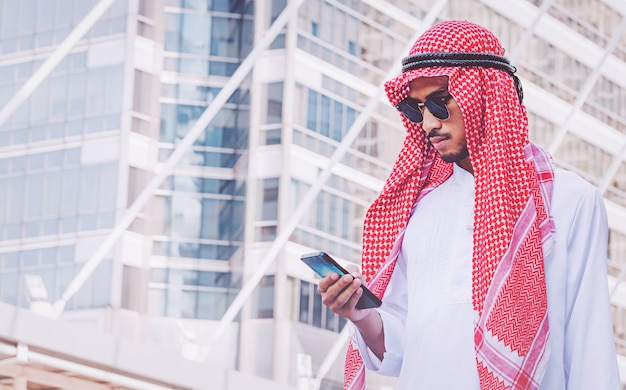アラブのビジネスマンが市内の携帯電話でメッセージング