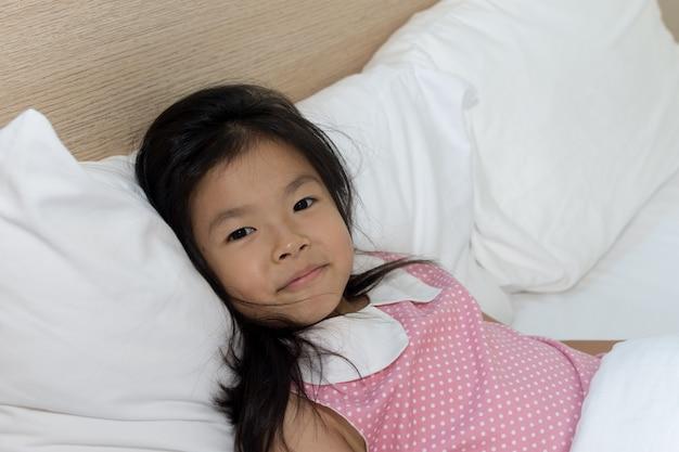 Азиатская маленькая девочка спит в постели