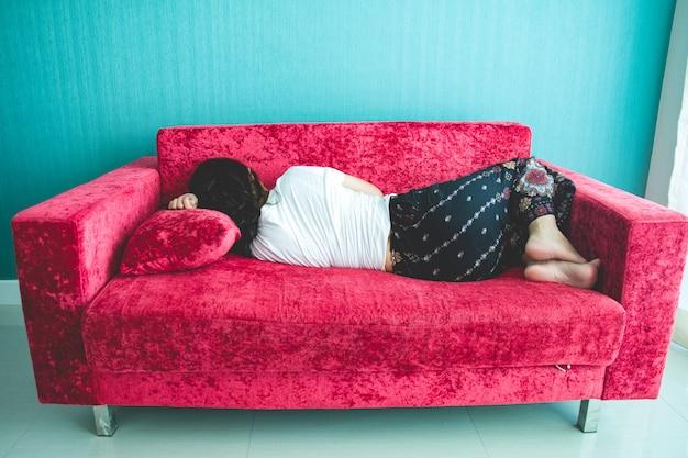 自宅のソファーで寝ている若い女性