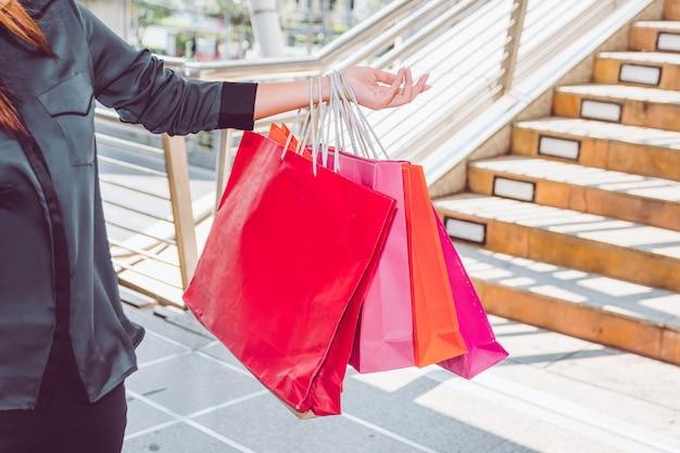 買い物を楽しんで買い物袋を持つ幸せな女