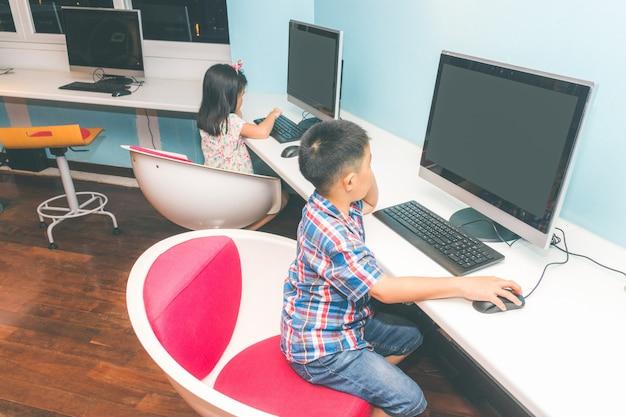 男の子と女の子がコンピューターで遊んで