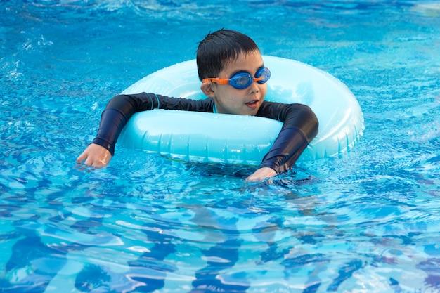 Молодой мальчик, плавание в бассейне.