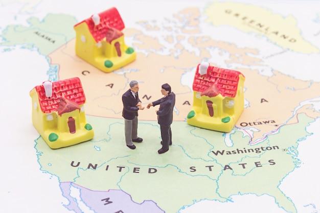 実業家とアメリカ地図上の家。ミニチュアの人々