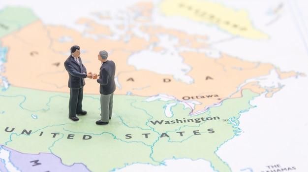 ミニチュアの人々、地図上に立っている実業家アメリカ人