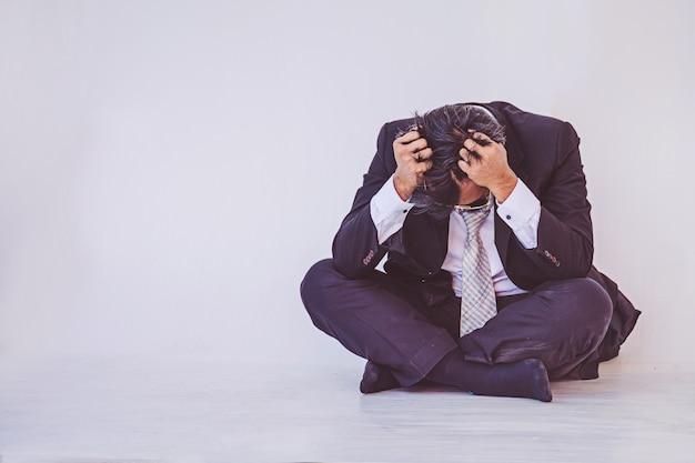 Депрессии бизнесмен, сидя на полу
