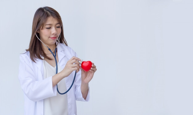 赤いハートを調べる聴診器を持つ医師