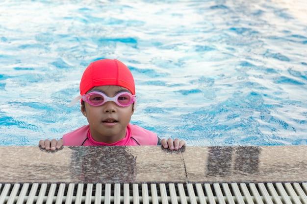 Молодая девушка, плавание в бассейне.