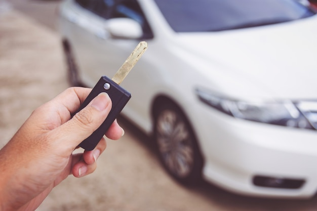 Мужчина держит ключи от машины с автомобилем