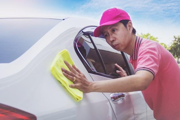 自動車サービススタッフがマイクロファイバーの布で車を清掃