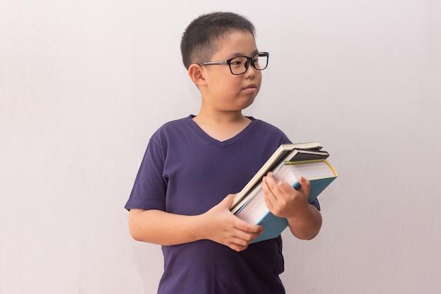 学校の準備ができている本を保持しているアジアの少年