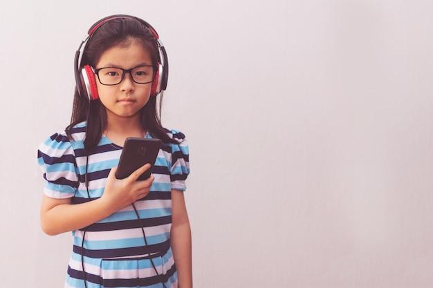 音楽を聞くヘッドフォンを持つアジアの少女