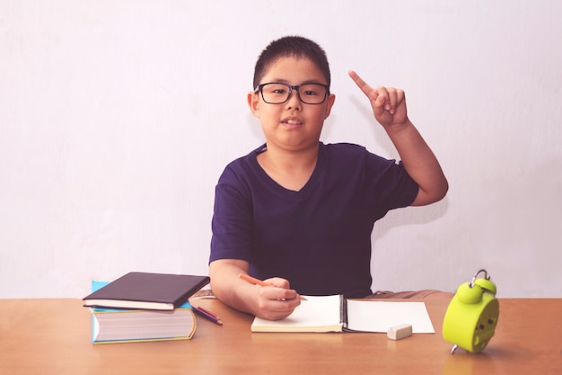 テーブルで本を書くアジアの少年