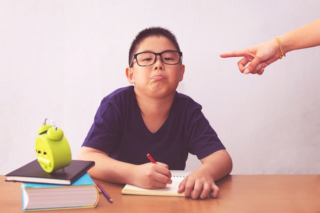 退屈で疲れたアジア学生の男の子が宿題をしています。彼を指している怒っている母親