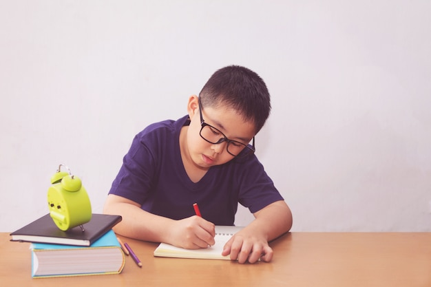 Азиатский мальчик пишет книгу на столе