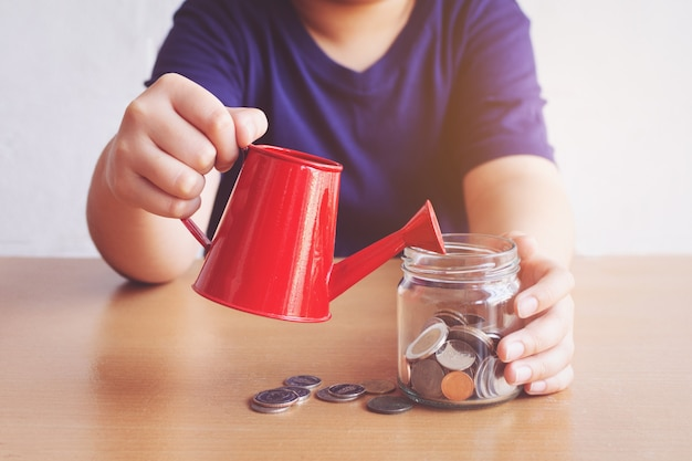コインに水をまく少年。お金の概念の計画