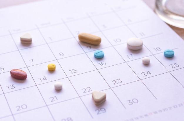 Куча различных таблеток на фоне календаря. концепция здравоохранение