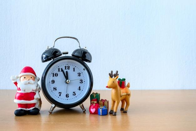 Санта-клаус и часы, олень и подарок на столе. с новым годом и рождеством