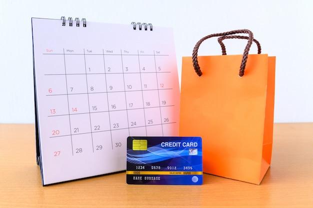 日とクレジットカードと木製のテーブルの上のオレンジ色の紙バッグカレンダー。ショッピングコンセプト