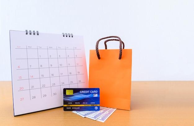 Календарь с днями и кредитной картой и оранжевой бумажной сумкой на деревянном столе. концепция покупок